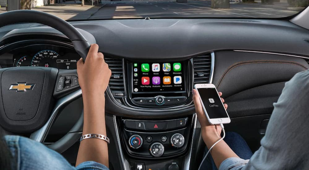 A woman has her iPhone connected to her 2020 Chevy vehicle while driving through Albany, NY.