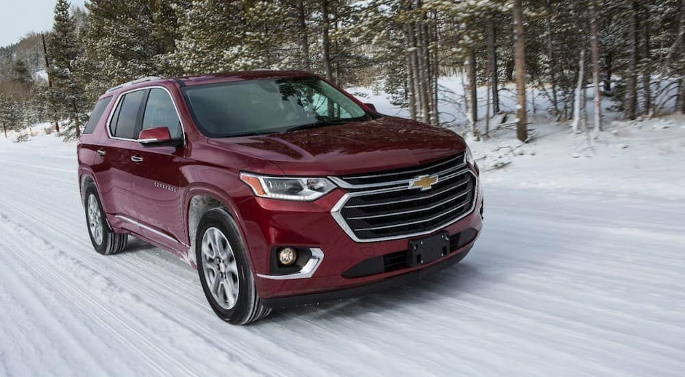 A red 2018 Chevy Traverse, a popular option for an all year vehicle at car dealerships in Albany, NY, is driving on a snowy road in a snow storm.