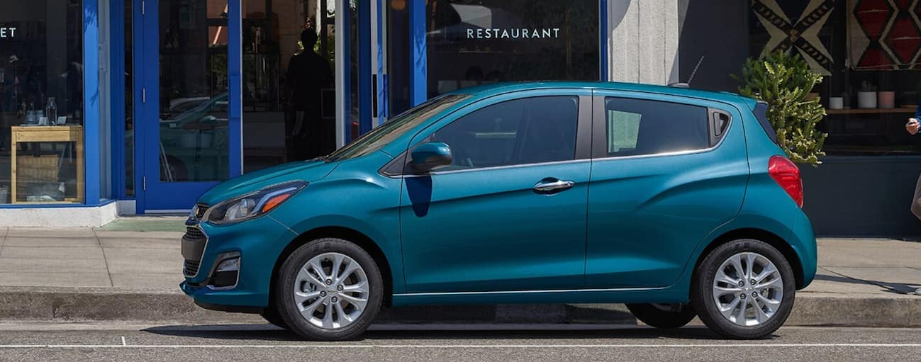 A blue 2020 Chevy Spark is parked on a road in front of restaurant near Albany, NY.