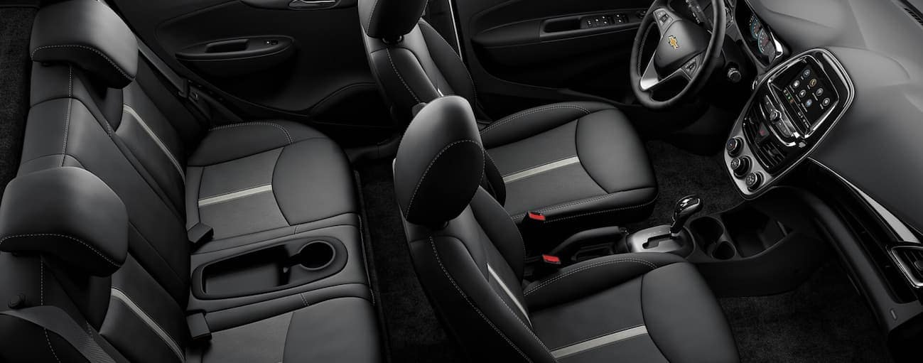 A birds eye view of the front and rear black leather interior of a 2020 Chevy Spark is shown.
