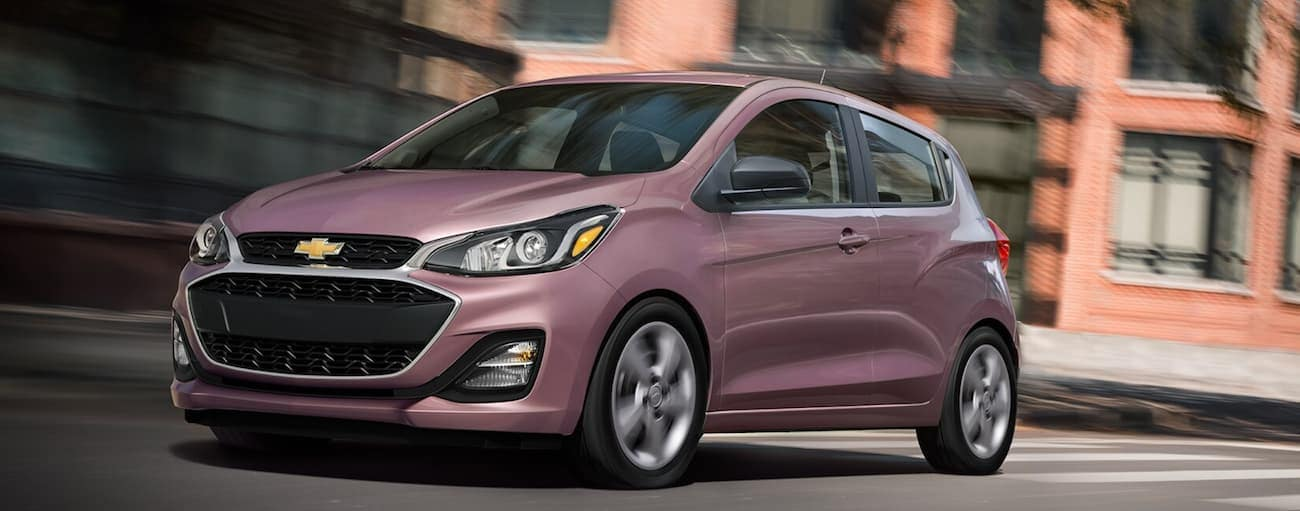 A light purple 2020 Chevy Spark is driving on a city street past brick buildings near Albany, NY>