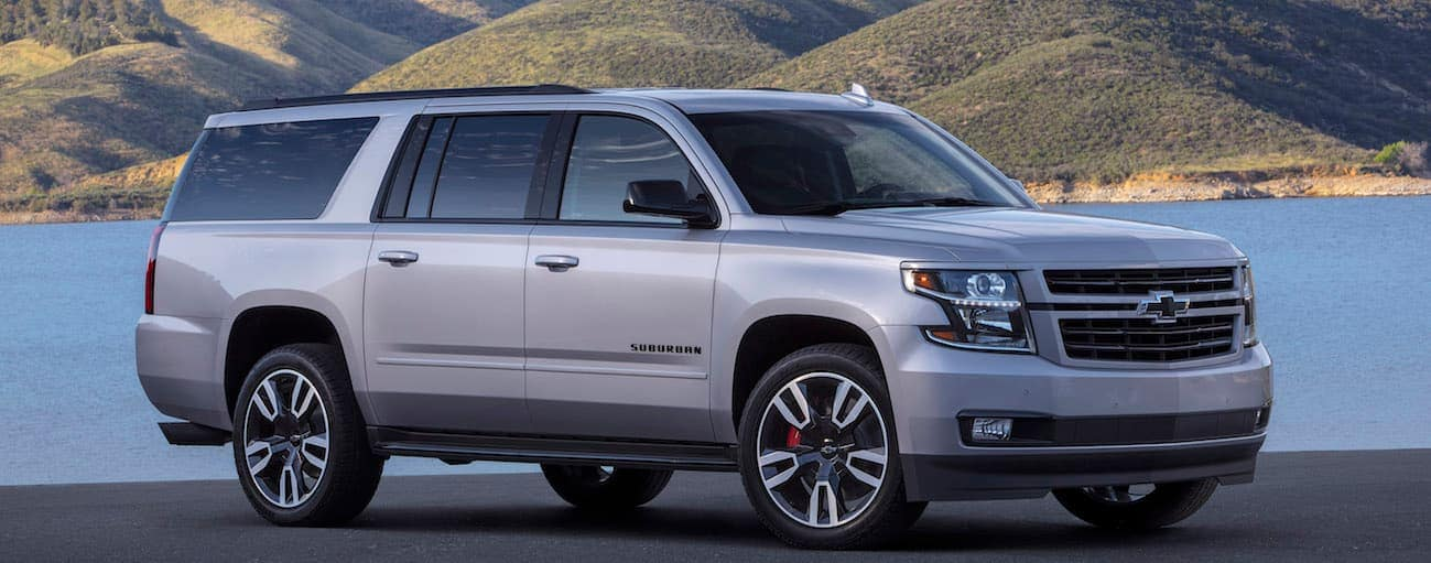 a silver 2020 Chevy Suburban RST Edition is parked in front of a lake and mountains outside of Albany, NY.