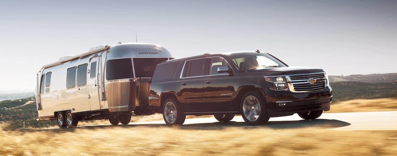 A black 2020 Chevy Suburban is towing an Airstream up a hill near Albany, NY.