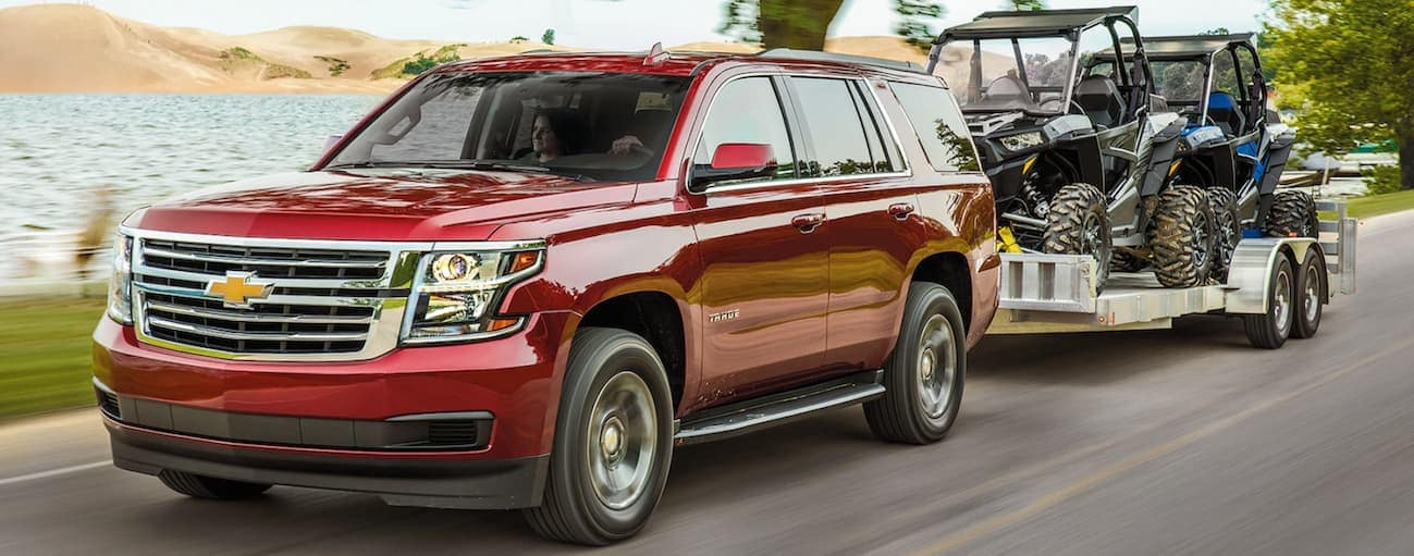 A red 2020 Chevy Tahoe is towing a trailer with 2 side by sides on it.