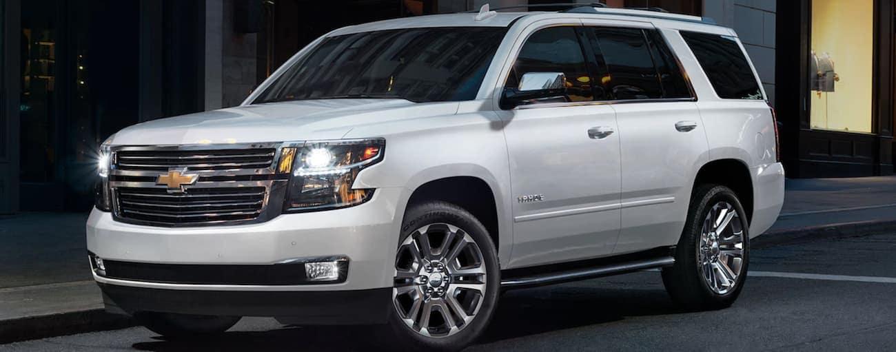 A white 2020 Chevy Tahoe is parked on a dark city street near Albany, NY.