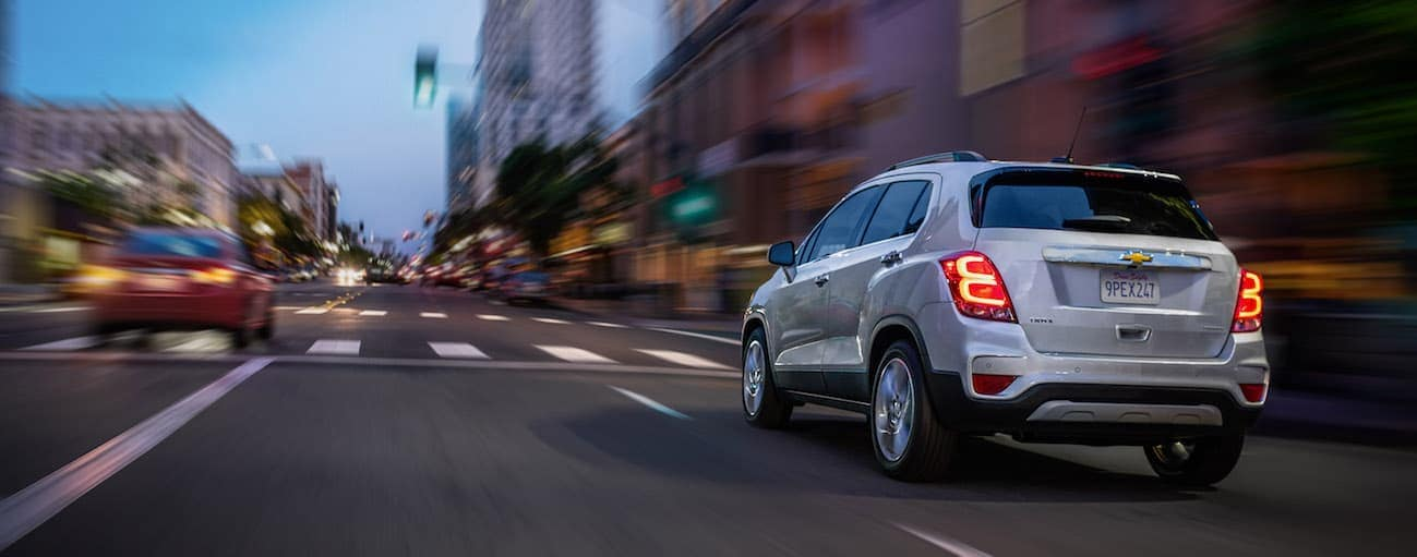 A silver 2020 Chevy Trax is driving on a city street past brick buildings near Albany, NY.