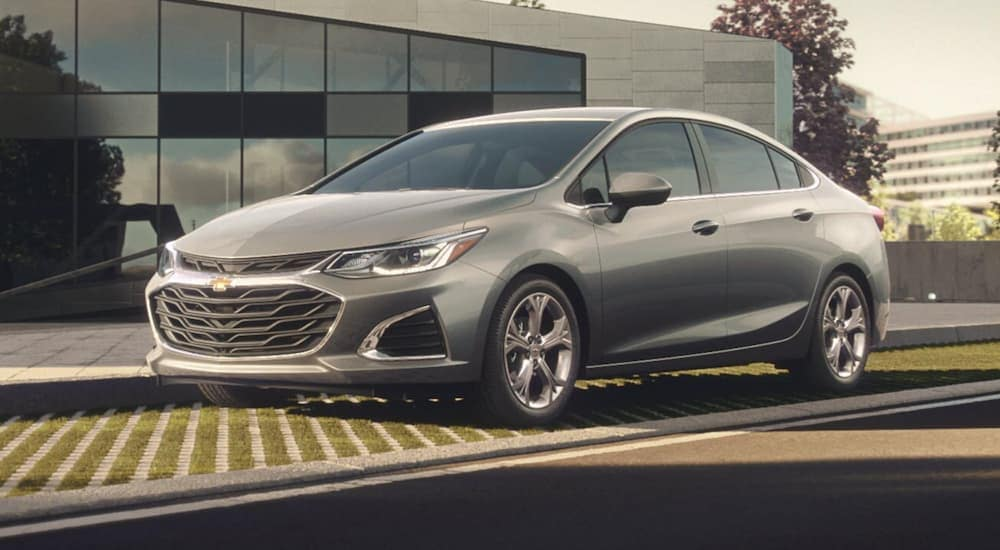 A grey 2019 Chevy Cruze, a favorite at car dealerships in Albany, NY with Teen Driver technology, is parked in front of an office building.