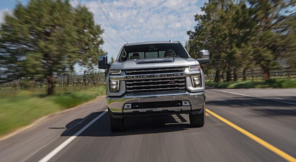 A silver 2020 Chevy Silverado 2500HD is driving on a tree-lined road after leaving one of our car dealerships in Albany, NY.