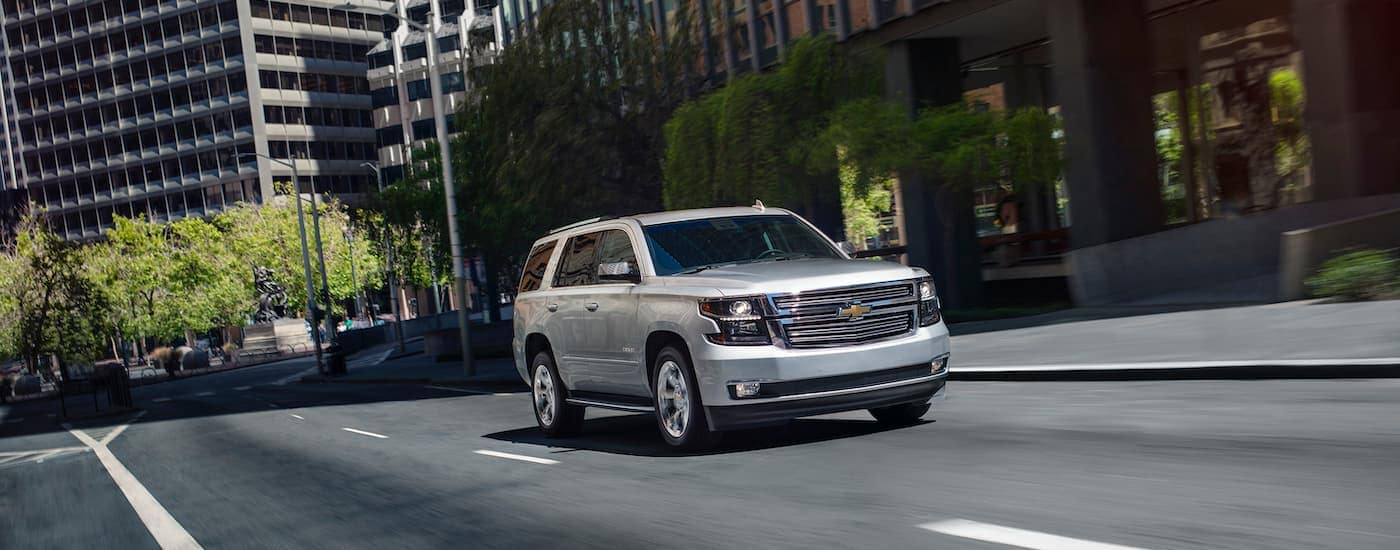 A silver 2020 Chevy Tahoe is driving down a city street.
