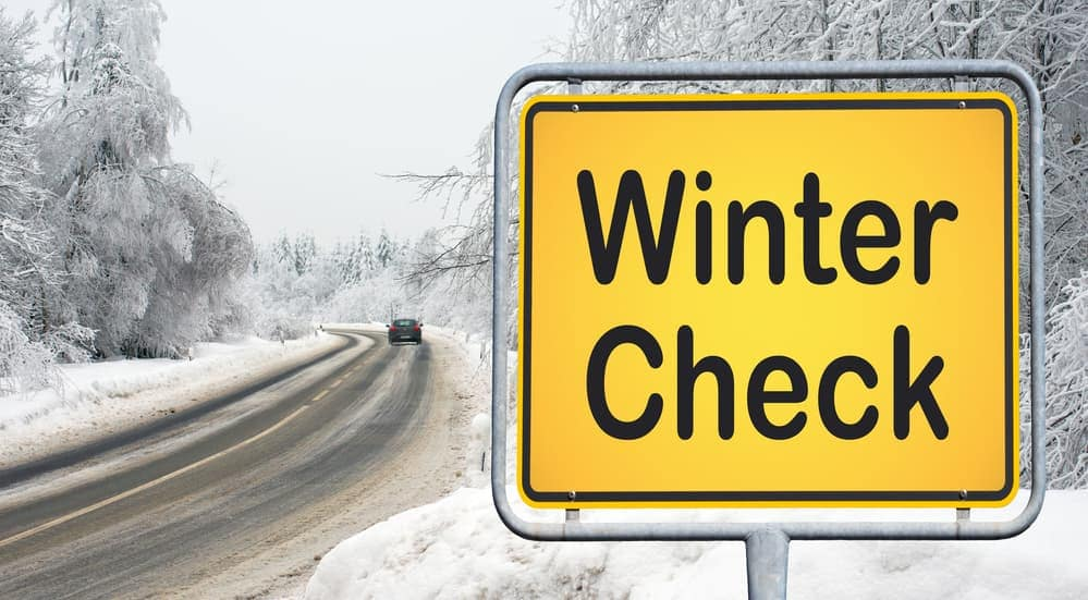 A winter check sign is shown in front of a snow covered road in Albany, NY.