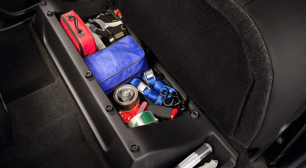 A storage compartment in a car is shown with important supplies needed incase your car breaks down.