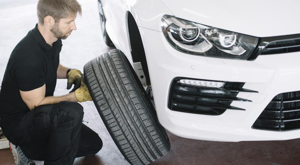 A mechanic is changing a customer's summer tires and putting winter tires on their vehicle, which can be done at any local car dealerships in Albany, NY.
