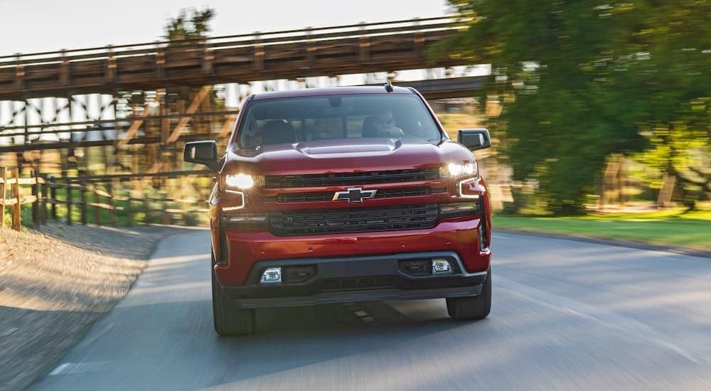 A red 2020 Chevy Silverado is driving past a train trestle after leaving a Chevy dealer in Albany, NY.
