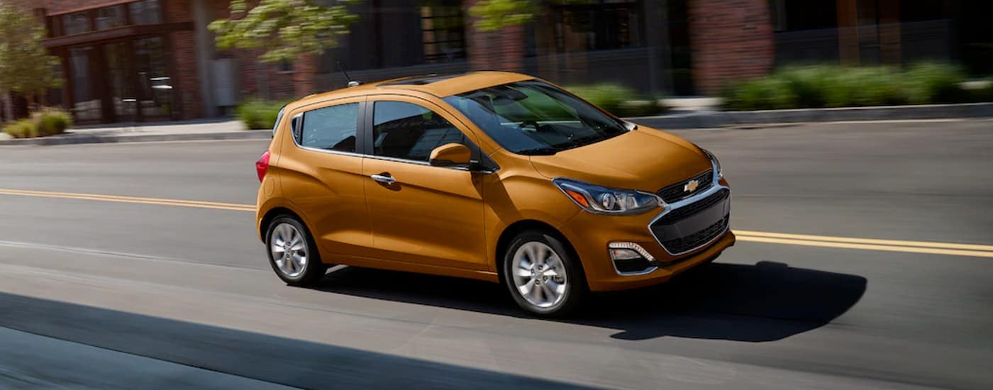 An orange 2020 Chevy Spark is driving past a brick building.