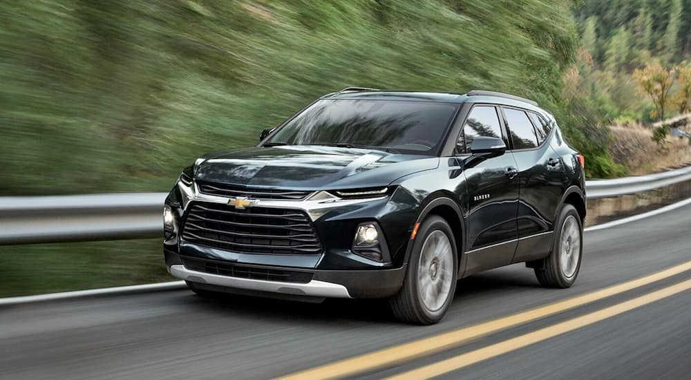 A dark green 2020 Chevy Blazer is driving on a tree-lined road near Albany, NY, after leaving a Chevy dealer near me.