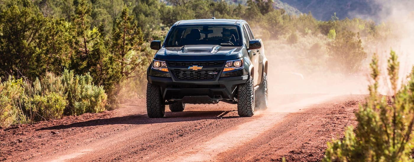 A black 2020 Chevy Colorado is driving on a dirt road.