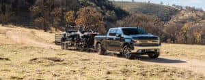 A black 2020 Chevy Silverado is towing a trailer with side-by-sides on a dirt road near Albany, NY.