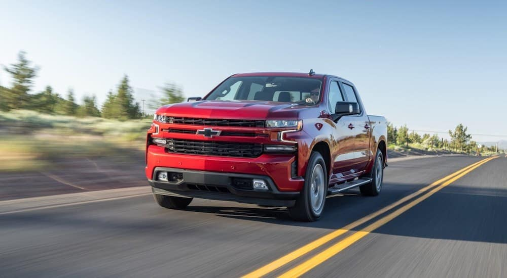 A red 2020 Chevy Silverado is driving on a road with pine trees behind it near Albany, NY.
