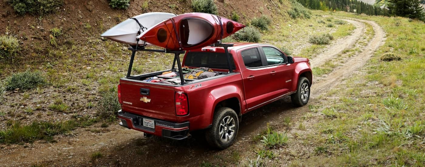 A red 2020 Chevy Colorado, popular among Chevy trucks in Albany, NY is off-road with kayaks.