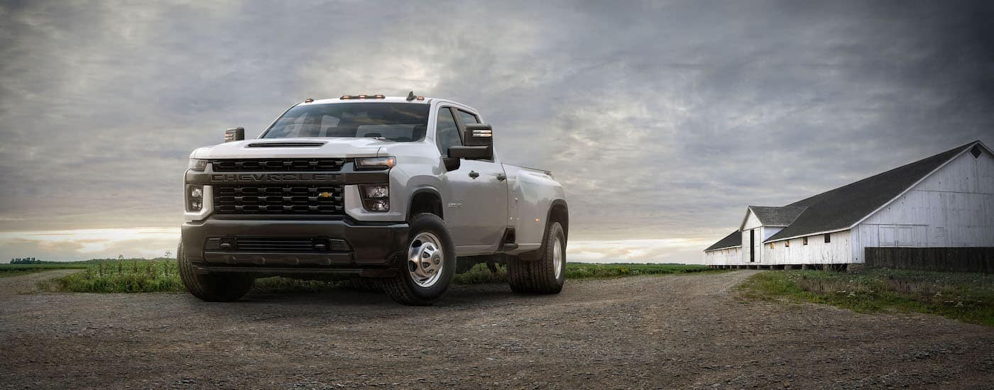 A white 2020 Chevy Silverado 3500HD is parked in front of a white barn.