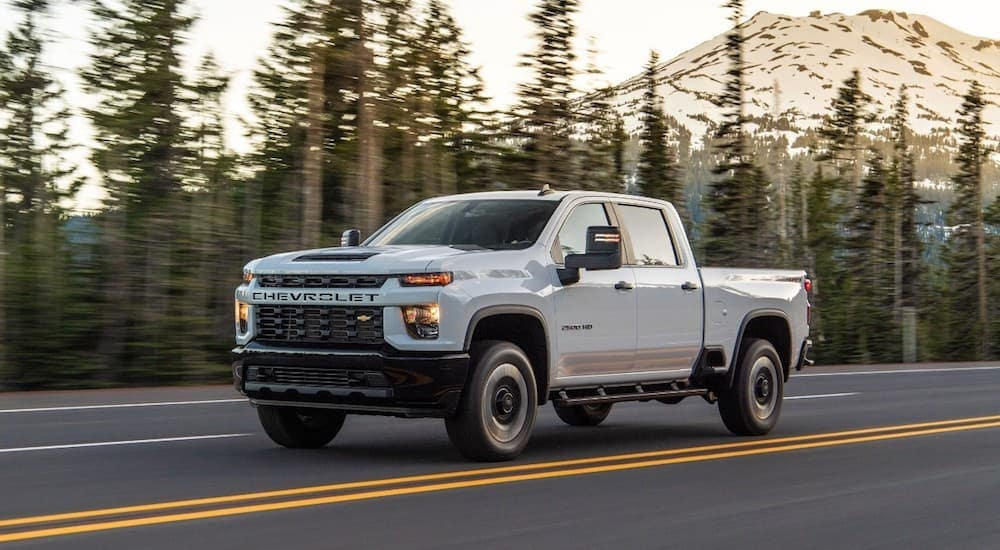 A white 2020 Chevy 2500HD is driving on a treelined road outside of Albany, NY.