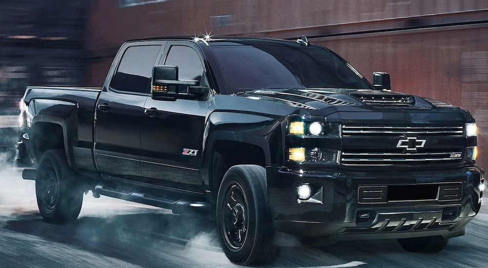 A black 2019 Chevy Silverado 2500HD, one of the best selling Chevy trucks in Albany, NY, is driving through rain.