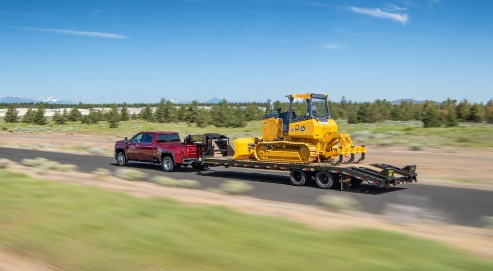A red 2020 Chevy Silverado 3500HD is towing heavy equipment using a gooseneck.