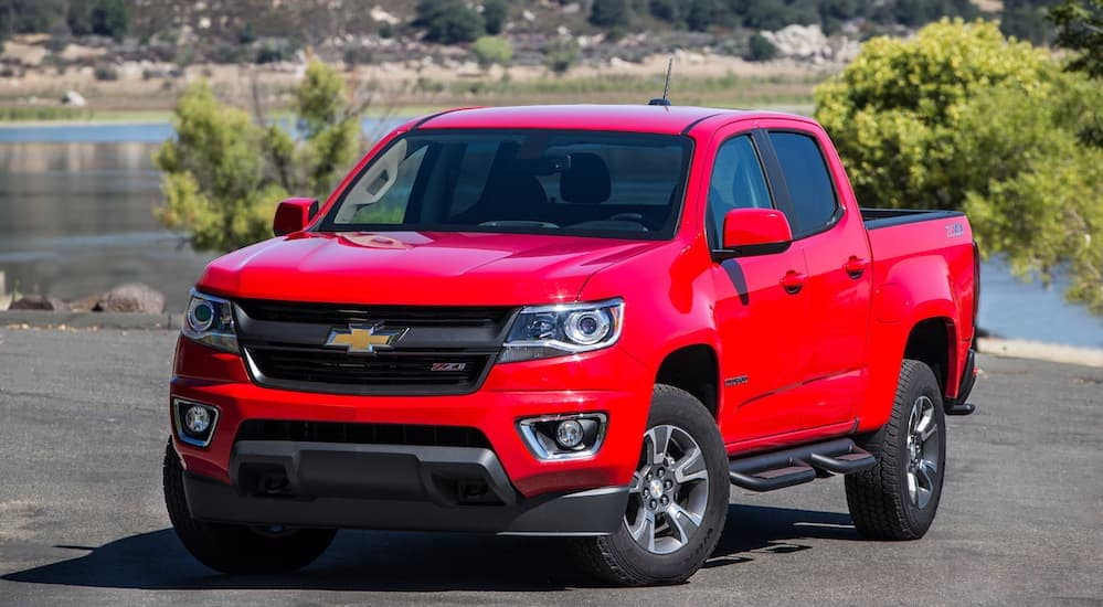 A red 2017 Chevy Colorado is parked in a parking lot with trees in the distance near Albany, NY.