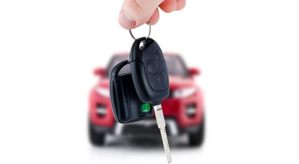 Keys are being held in front of a blurry red SUV.