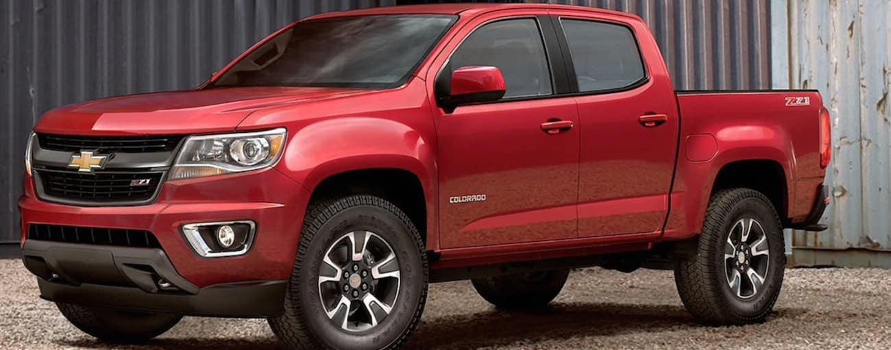 A red 2020 Chevy Colorado is parked on a gravel parking lot.