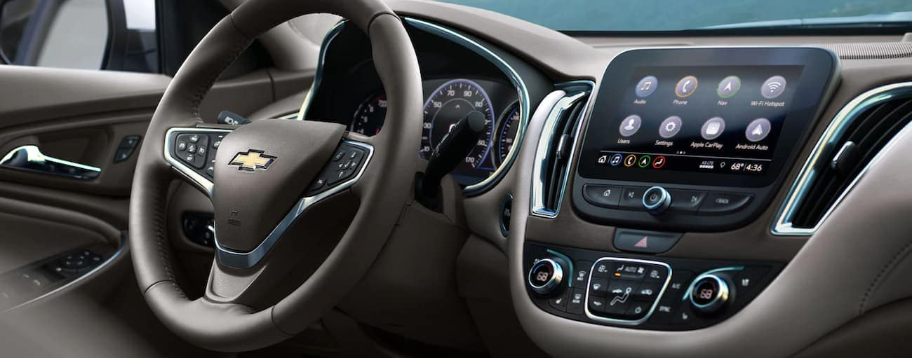 A close up of the black and tan interior of a 2020 Chevy Malibu is shown with a touchscreen.