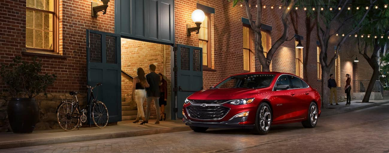 A red 2020 Chevy Malibu is parked in front of a brick building on a lit up dark side city street.