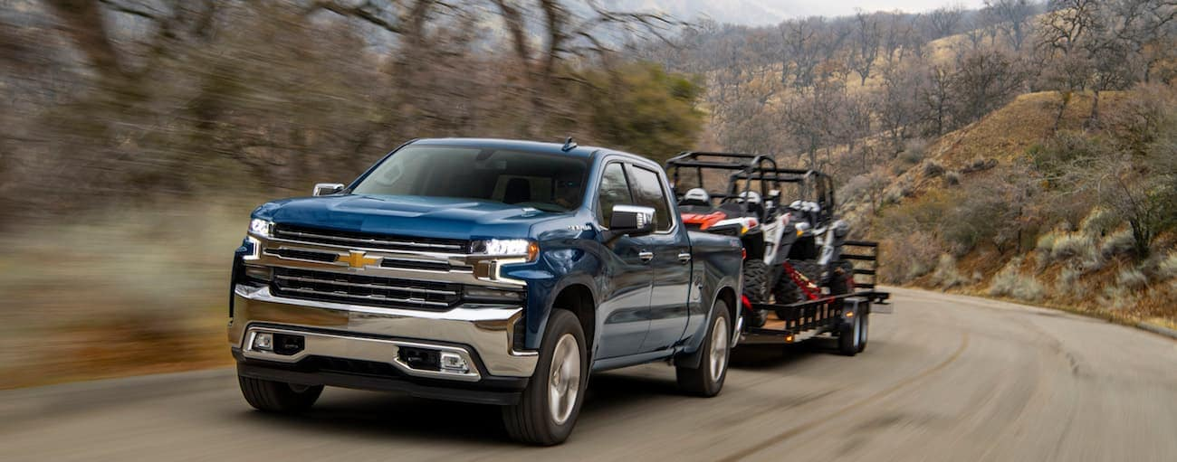 A blue 2020 Chevy Silverado 1500 is towing a trailer loaded with two side by sides on a dirt road near Albany, NY.