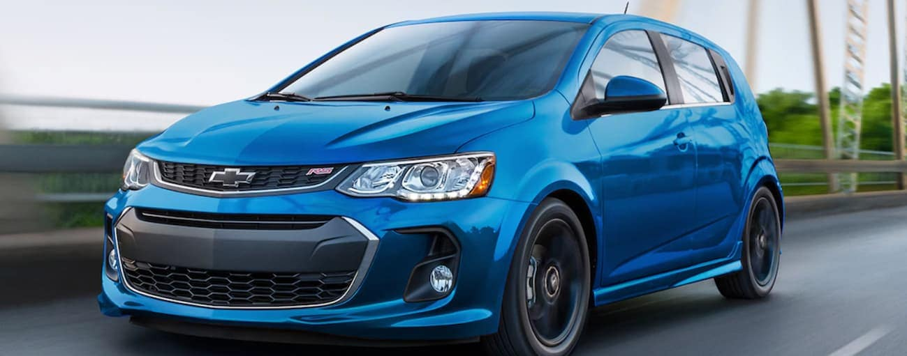 A blue 2020 Chevy Sonic RS is driving on a highway near Albany, NY.