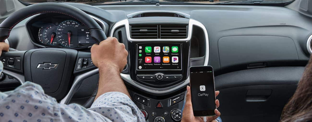 a close up of the front interior of a 2020 Chevy Sonic while a couple is using their Apple phone to connect to the Apple Carplay.