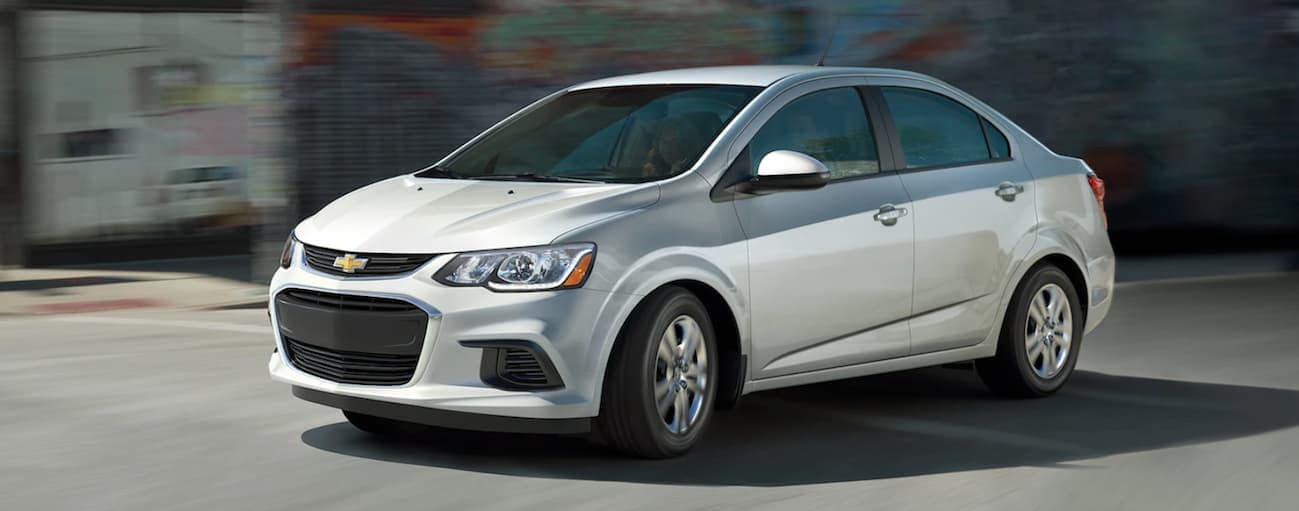 A silver 2020 Chevy Sonic sedan is driving on a city street near Albany, NY.