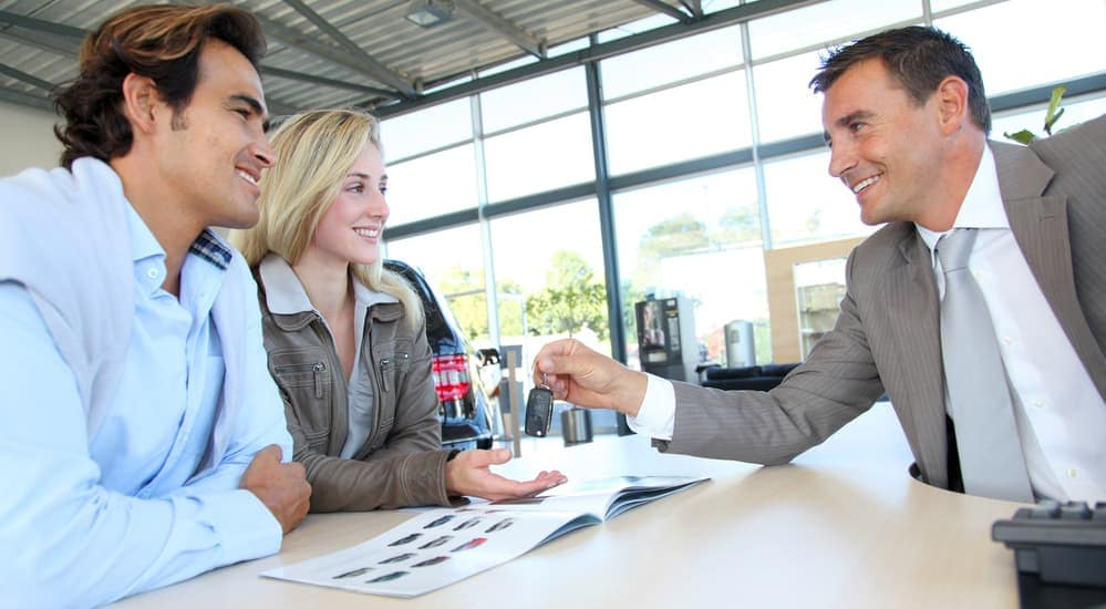 A smiling salesman is helping a couple at our Albany car dealership