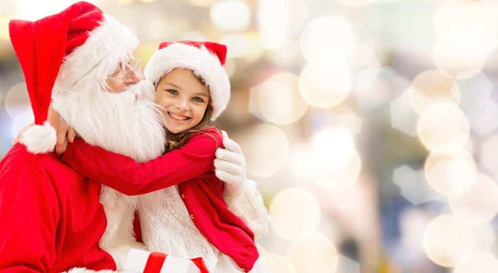 A girl is sitting with Santa with a blurred, bright background.