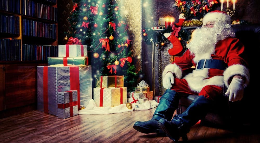 Santa is sitting in front of a tree with presents at an Albany, NY home.
