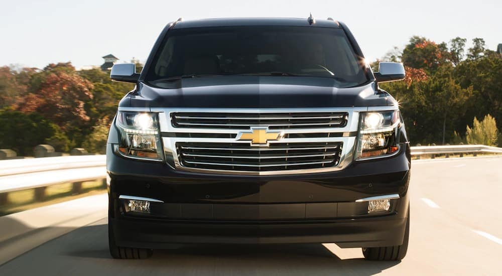 A close up of the front end of a black 2020 Chevy Suburban driving on a road outside of Albany, NY.