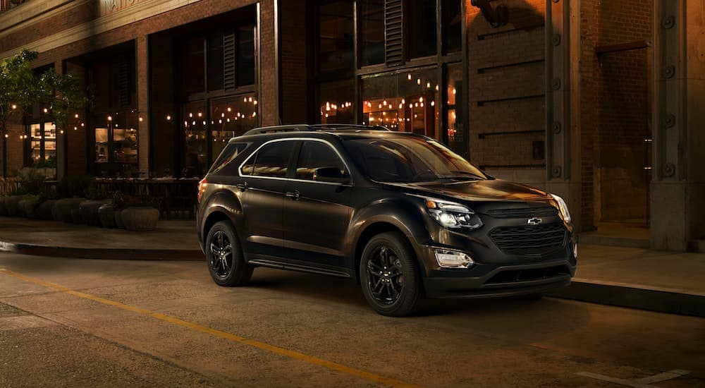 A black 2017 Chevy Equinox, which is a popular option among used cars for sale in Albany, NY, is parked next to a restaurant at night.