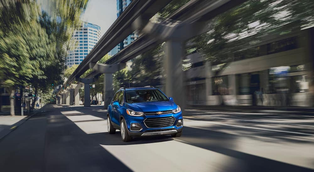 A blue 2017 Chevy Trax is driving next to a highway near Albany, NY.