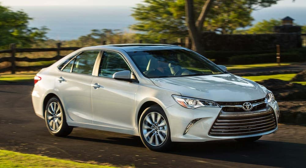 A white 2017 Toyota Camry is driving on a treelined road near Albany, NY, at dusk.