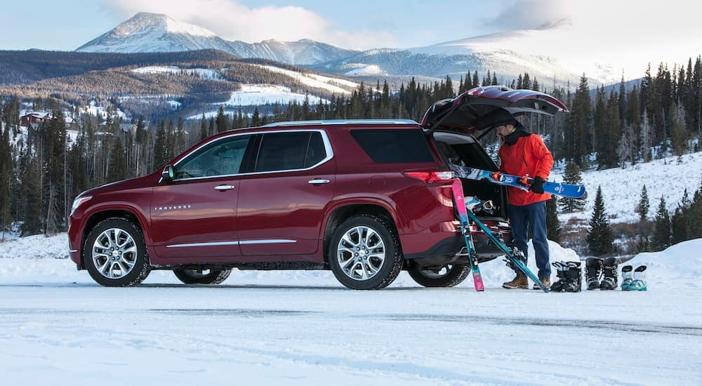 A man is unloading ski gear out of the back of this red 2017 Chevy Traverse near Albany, NY.