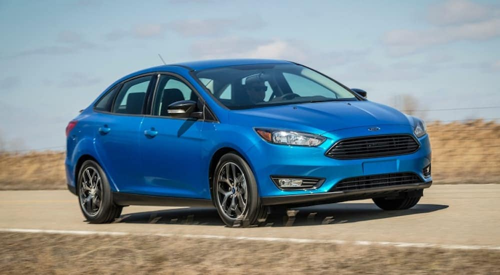 A blue 2018 Ford Focus is driving on a grass lined during the sunny day.