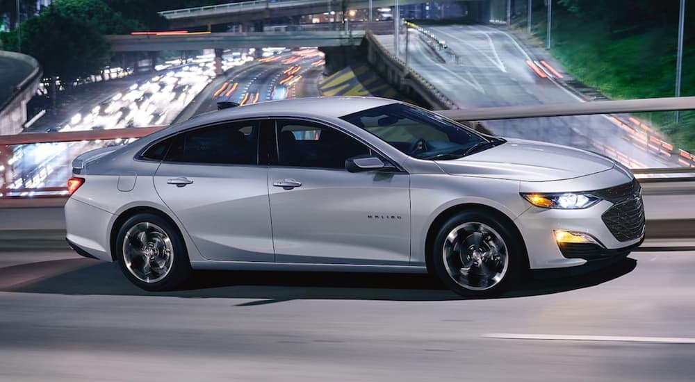 A silver 2019 Chevrolet Malibu, which is a popular used car at car dealerships near me, is driving over a busy highway at night.