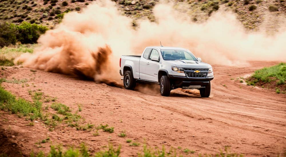 A white 2020 Chevy Colorado, which is a popular truck at a Chevy dealer near me, is drifting on a dirt road while a dirt cloud rises behind it.