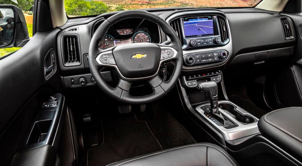 The front black and grey interior of a 2020 Chevy Colorado ZR2 is shown with an infotainment system and a drivers display.