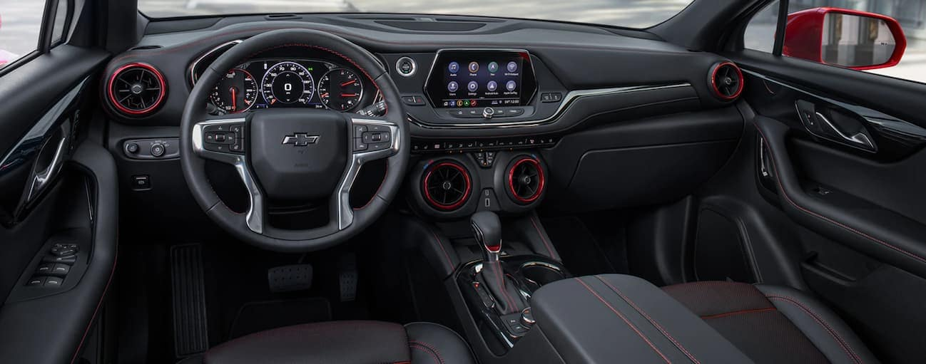 The front black and red leather interior of a 2020 Chevy Blazer is shown with an infotainment system.