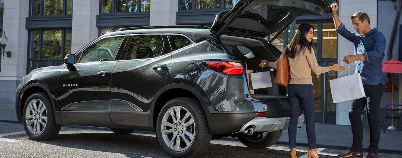 A green 2020 Chevy Blazer has the tailgate open while a smiling couple puts shopping bags in the trunk.